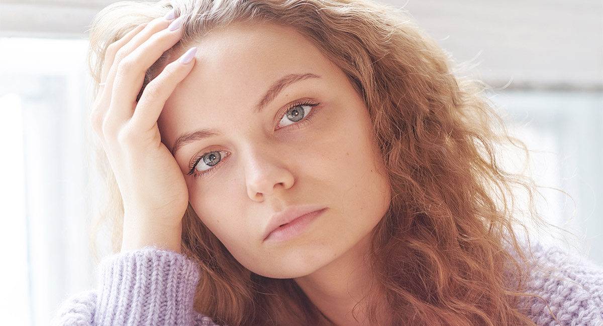 Depressed young woman near window at home, closeup   Image